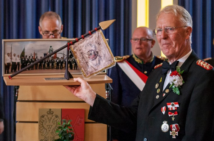 """40 Jahre hat Ehrenvizefeldwebel Gerhard Schulz die Fahne der 2. Kompanie getragen. Am Wachtag übergab er sie nun in jüngere Händen. Vom Bataillon wurde er für seine Leistung mit dem Eintrag ins Ehrenbuch bedacht, von den Fahnengruppen erhielt ihr Sprecher ein Erinnerungsgeschenk mit """"seiner"""" Fahne der 2. Kompanie."""