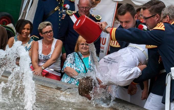 """Vier Kameraden des Mindener Tambourkorps mussten sich im Brunnen auf dem Kleinen Domhof der """"Tambour-Taufe"""" unterziehen. """"Toni der Trobimmler"""" wurde dabei sogar vom Stadtmajor getauft."""